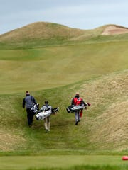 A trio of golfers walk to the fairway after teeing off on the first hole during a Fox River Classic Conference meet in April at Whistling Straits.