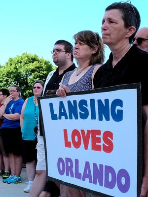 Nikki Joly, holds a sign showing Lansing support for the victims of the mass shooting in Orlando, Florida Sunday, June 12, 2016 at the state Capitol. About 120 people attended the event organized by the Lansing Association of Human Rights.