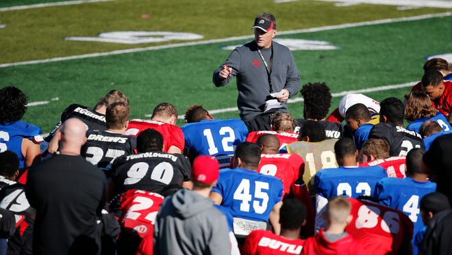 Utah head football coach Kyle Whittingham speaks with his players after football practice Wednesday, Dec. 16, 2015, in Las Vegas.