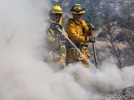 LA County firefighter mop up an area burned by the Blue Cut Fire on the eastern edge of Wrightwood on Thursday, August 18, 2016