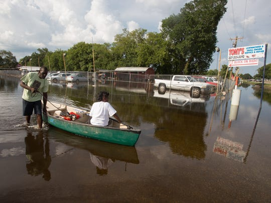 Frederick Moore transports Porsha Evans by boat in the Derby Heights neighborhood near the Lafayette/Breaux Bridge border August 24, 2016.