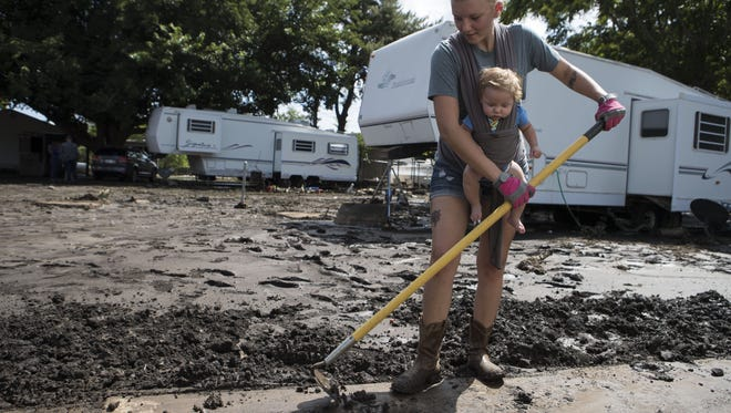 Sammiy Baca sweeps mud with her son Michael Baca-Waldren, 4 months, at the Chimney Ranch Mobile Home Park on July 20, 2017, in Mayer, Arizona.