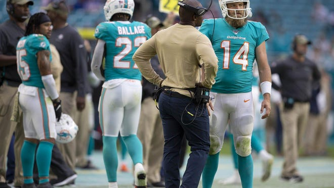 Miami Dolphins head coach Brian Flores talks with Miami Dolphins quarterback Ryan Fitzpatrick (14) after a failed two point conversion during a game November 17.