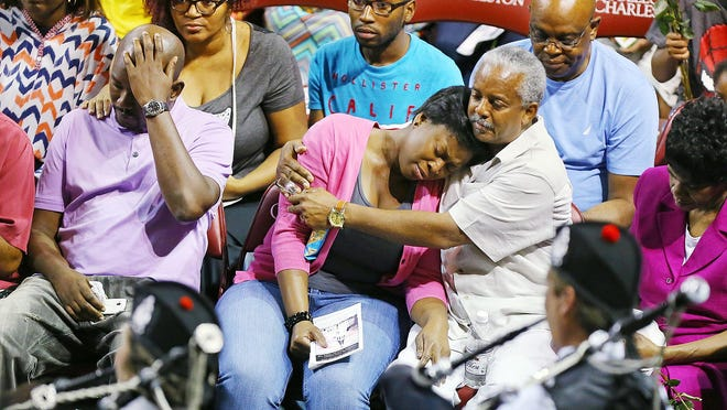 """Family members of the shooting victims react as the Charleston Pipe and Drum play """"Amazing Grace"""" at the beginning of a memorial service for the nine people killed in a shooting at Emanuel AME Church, Friday, June 19, 2015, in Charleston, S.C."""