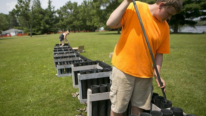Ryan Jones of Ripon cleans out plastic tubes Sunday at Mead Park in preparation for the fireworks display for Riverfront Rendezvous in Stevens Point.