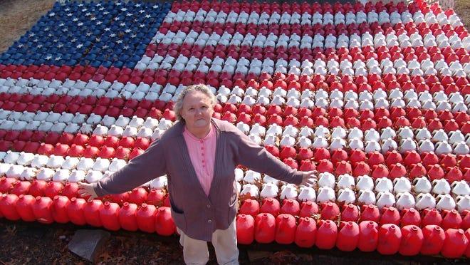 Josephine Stapleton stands in front of her milk jug flag.
