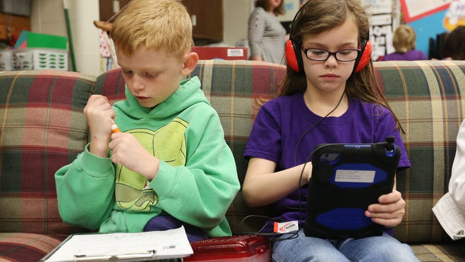 """Aidan Rowe does """"morning work"""" and Kinsley Creach uses a tablet in their first-grade classroom at Wilder Elementary. The classroom is part of the Ignite initiative, which is testing ways to integrate technology into the teaching and learning."""