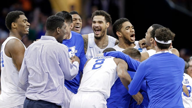 Kentucky players celebrate after a 68-66 win over Notre Dame in a college basketball game in the NCAA men's tournament regional finals, Saturday, March 28, 2015, in Cleveland. The 38-0 Wildcats advanced to the Final Four.