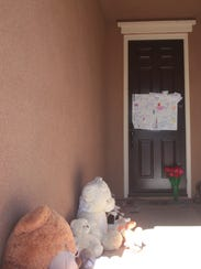 Teddy bears and flowers have been placed outside the