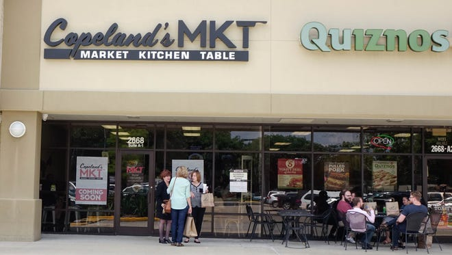 Patrons gather and eat outside during the soft opening of Copeland's MKT in Lafayette Friday, June 9, 2017.