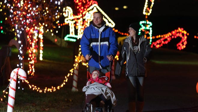 Matt Portka, left, his wife Autumn Portka, and their daughter Alina Portka, 2,  of Dover, walk through Christmas Magic at Rocky Ridge Park last year.