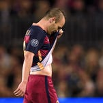 Barcelona's midfielder Andres Iniesta leaves the field after being injured during the UEFA Champions League football match FC Barcelona vs Bayer Leverkusen.