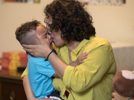 Eva Sanchez kisses her son Adael Manon, 19-months-old,