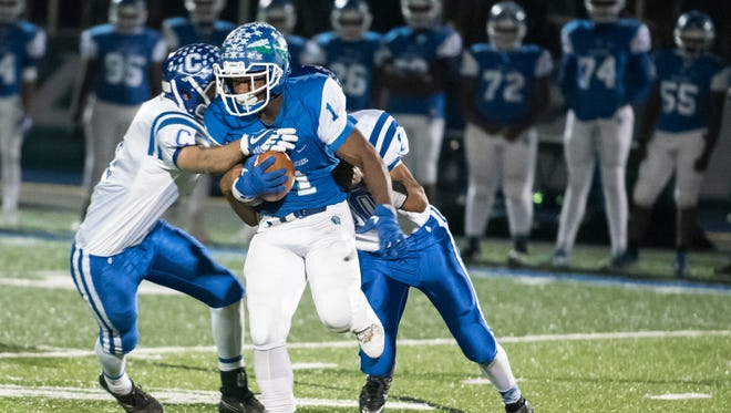 Cornell Beachem of Winton Woods carries the ball against Chillicothe defenders in the Division II regional quarterfinal Nov. 3. Winton Woods won 61-27.