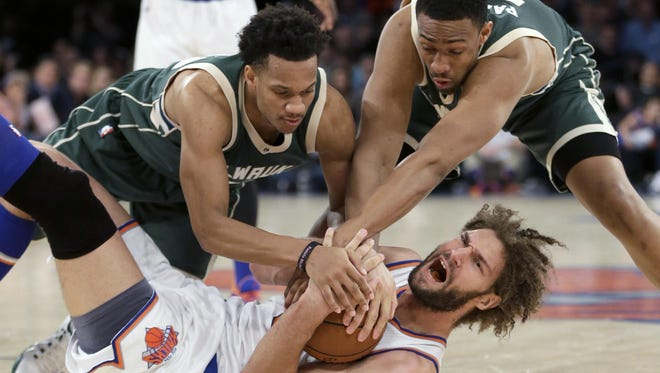 Rashad Vaughn (left) and Jabari Parker of the Bucks swarm Robin Lopez of the Knicks in a game last year.