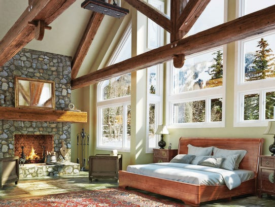 Large windows, wood beams and a stone fireplace bring