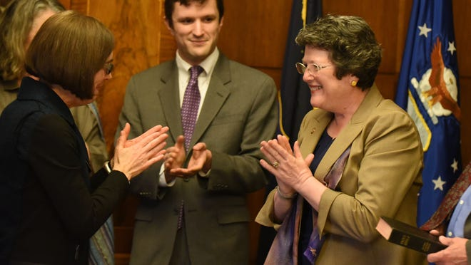 Gov. Kate Brown (left) congratulates Jeanne Atkins after she is sworn in as Oregon Secretary of State during a ceremony on Wednesday, March 11, 2015, at the Oregon State Capitol in Salem. Atkins was joined by her sister, Terry Anne Paquette; son, John P. Atkins (center); and husband, John Atkins.