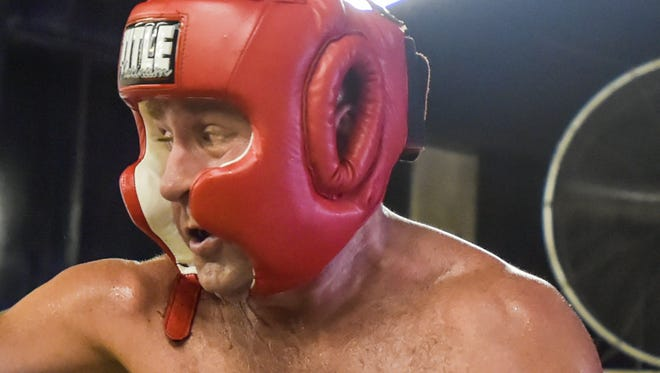 Clay Higgins, right, swings a big right during a sparring session with Jesse Saloom on Sunday at the Ragin' Cajun Boxing Club in Lafayette.