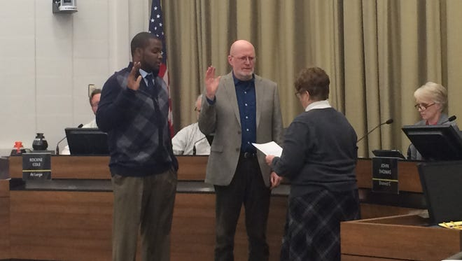 Kingsley Botchway, left, and Jim Throgmorton, center, are sworn in as mayor pro tem and mayor respectively during an Iowa City Council meeting Monday.