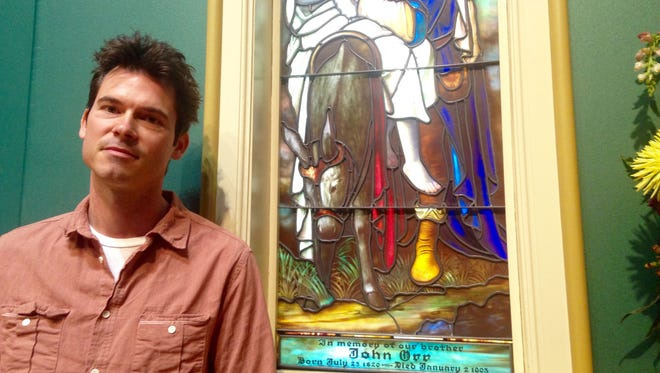 Ketch Secor of Old Crow Medicine Show poses for a photo beside a stained glass window inside St. Ann's Episcopal Church in East Nashville.