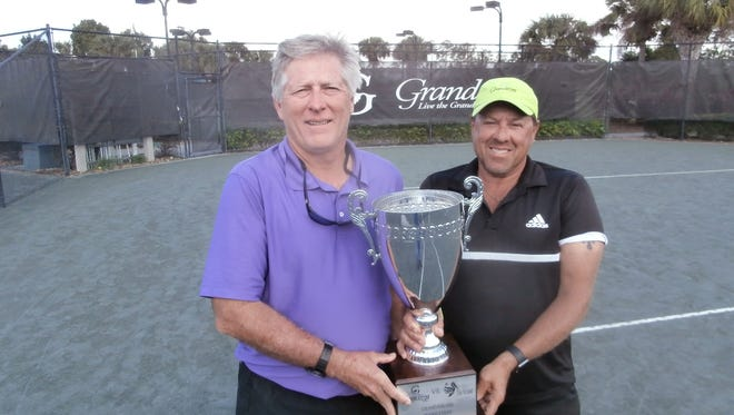 Tennis directors Jim Katterfield (left) of The Club at the Strand and Dave DeKeersmaker of The Club at Grandezza show the trophy their members will compete for on Feb. 5.