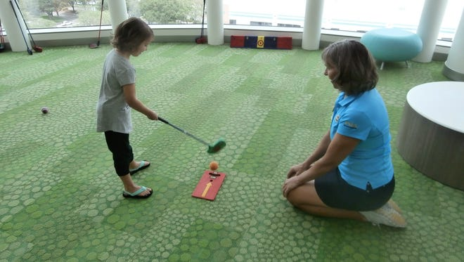 Sophia Cameratta, 6, lines up a putt under the guidance of PGA pro Robin Albright of Cypress Lake Country Club during Smiling Fore Life program event at the Golisano Children's Hospital of Southwest Florida.