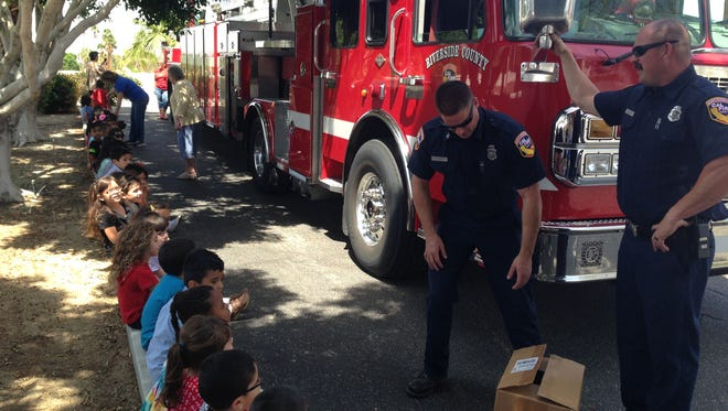 Firefighters visit a Desert Sands preschool where they talk with students about fire prevention and safety. The box at their feet contains plastic fire helmets which they distributed.