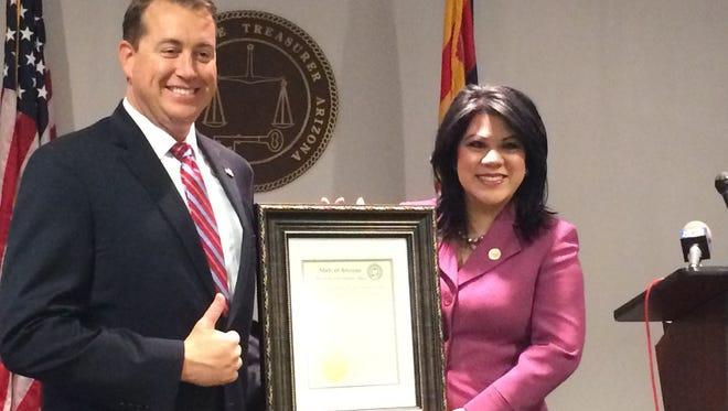 "Arizona Treasurer Jeff DeWit presents State Sen. Kimberly Yee with a ""Hero of the Arizona State Treasurer's Office"" award, the first award of its kindon Thursday, Sept. 7, 2017."