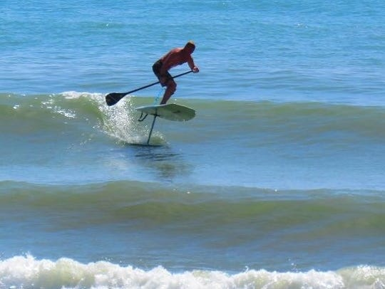 Wyett Wernth uses a standup paddleboard to hydrofoil