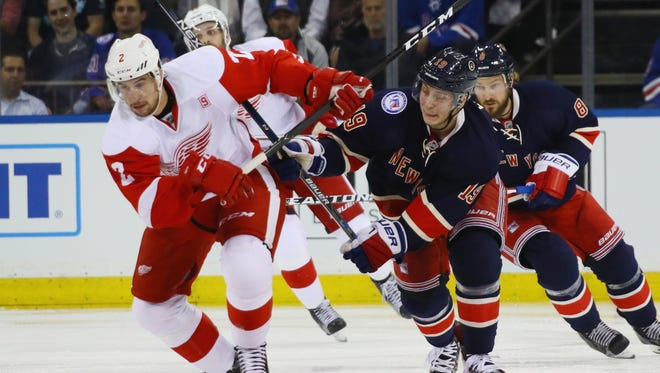 Brendan Smith #2 of the Detroit Red Wings and Jesper Fast #19 of the New York Rangers pursue the puck during the second period at Madison Square Garden on October 19, 2016 in New York City.
