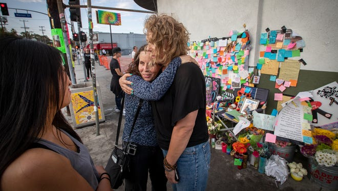 In this July 31 photo, MaryLinda Moss and Lynne Westafer, right, hug at a memorial outside the Trader Joe's in Silver Lake neighborhood of Los Angeles, where they were held hostage during a standoff on July 21.