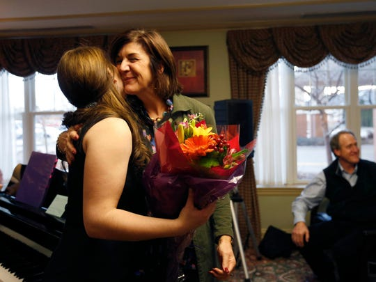 Haley Jenkins (left) gets a hug and a bouquet from mother Julianna Jenkins Jan. 29, 2016, following her first official performance at the Deerfield retirement community in Urbandale. Haley, a senior at Drake University, is living at the retirement community for a semester as part of an artist-in-residence program.