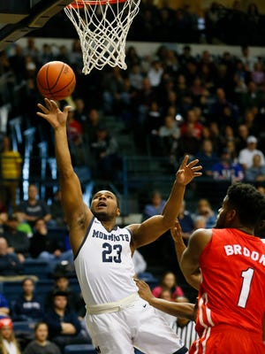 Monmouth Hawks guard Austin Tilghman (23) drive to the basket against Marist Red Foxes center Kentrall Brooks (1) during first  half  at Ocean First Bank Center, Monmouth University. 
