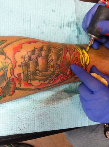 In about 90 minutes, fields in this maritime scene of a ship under sail, on the leg of Chris Owens, were filled in with color by artist Kip Grangier.