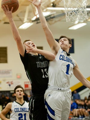 Trinity guard Justin Powell puts a shot up as Covington Catholic forward C.J. Fredrick defends the basket.