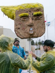 Tone Rubio, back, was one of the artists who created a Donald Trump puppet, which was part of the Día de Resistencia march in Coachella, Friday, Jan. 20, 2017.