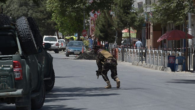 A member of the Afghan security forces walks on the street at the site of a suicide blast near Iraq's embassy in Kabul on July 31, 2017.