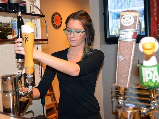 Chelsy Spicer pours one of the many micro brewery beers available on tap at the new bar just added to Cafe A Go Go. Photo taken 12/12/16.
