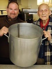 Mike Bievenour, left, Scout Master of Scout Troop No. 149 of Bethesda United Methodist Church in Salisbury, is joined by former Scoutmaster Delbert Maurice Davis, in holding one of several pots used to prepare the annual Scout spaghetti dinner.
