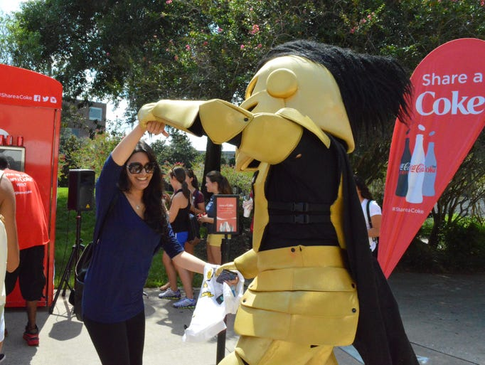 Knightro dances with a student while waiting in line
