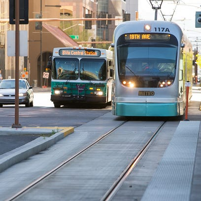 A city bus and light rail train at Van Buren St. and