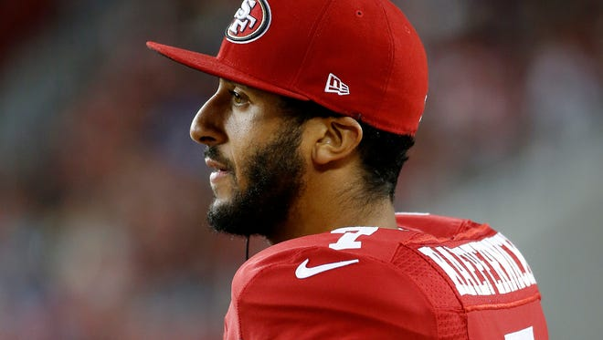 In this Sept. 3, 2015 file photo, San Francisco 49ers quarterback Colin Kaepernick watches from the sideline during the second half of an NFL preseason football game against the San Diego Chargers in Santa Clara, Calif. Kaepernick's decision this week to refuse to stand during the playing of the national anthem as a way of protesting police killings of unarmed black men has drawn support and scorn far beyond sports.