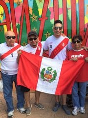 Peru-born Luis Giraldez holds up his country's flag
