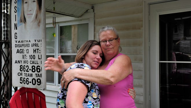 Debra Tuders hugs her daughter Jamie Pulley on the porch of Tuders' Lillian Street home. Police received an anonymous tip that Tuders' other daughter, Tabitha, was in Fremont, Neb.