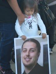 Jayla Chavez, 3, holds a photo of Paul Gilbert Morales,