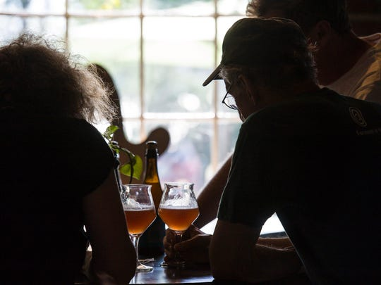 Bill Mares, center, and Todd Haire, right, collaborators in producing House of Fermentology sour beers, consider their product at Foam Brewery in Burlington on Friday, August 5, 2016.