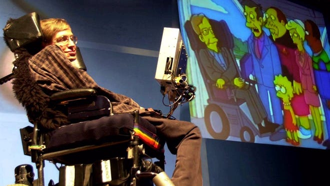 "British physicist Stephen Hawking looks, on his screen, at an animated clipping of himself with cartoon characters from ""The Simpsons"" during a public lecture in 2001."