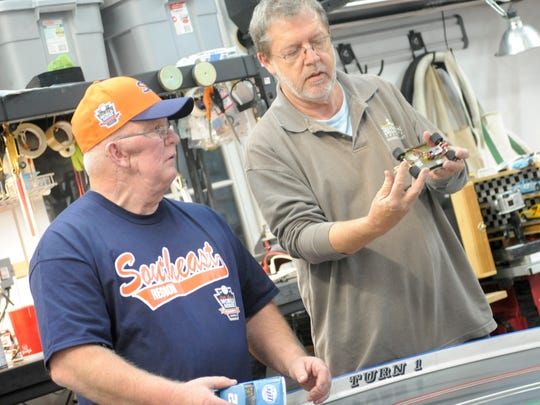 Dave Parrish, left, and Tom Campbell talk about a slot car on Thursday, Oct. 30 inside the garage of Lynn Combs.