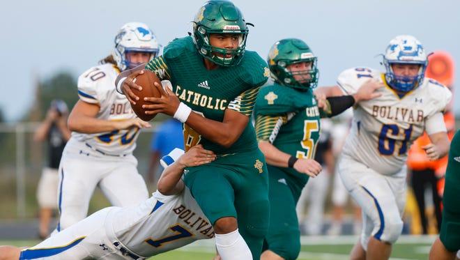Springfield Catholic quarterback Tyson Riley shakes off Bolivar defender Jonathan Vance during their game at Springfield Catholic High School on Friday, Sept. 15, 2017.