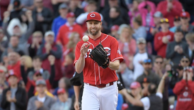 Cincinnati Reds pitcher Scott Feldman catches a ball tossed to him by Cincinnati Reds first baseman Joey Votto after the final out of a baseball game, Sunday, May 7, 2017, in Cincinnati. Feldman pitched a complete game as the Reds won 4-0 to complete a three-game sweep. (AP Photo/Michael E. Keating)
